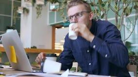 滑稽的疯狂的程序员用咖啡因瘾饮用的咖啡和快速地键入在膝上型计算机在办公室 4K 股票录像