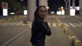 滑稽的白肤金发的女孩步行在都市街道的夜,自由跳舞下 摆在为照相机的微笑的妇女 影视素材