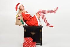 滑稽的白肤金发的妇女在圣诞老人在白色背景穿衣 库存图片