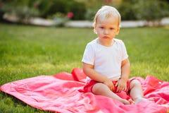 滑稽的白肤金发的小孩男孩在夏天庭院里 库存照片