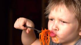 滑稽的白肤金发的男孩在他的兄弟旁边吃韩国红萝卜沙拉在厨房里 孩子一起是愉快的 股票视频