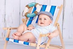 滑稽的矮小的小孩坐deckchair 免版税库存照片