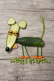 滑稽的老鼠由黄瓜和豌豆制成在木头 免版税库存图片