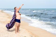 滑稽的肥胖超级英雄在海的岸站立 免版税库存照片