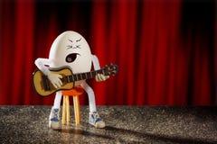 滑稽的蛋吉他弹奏者弹吉他 库存照片