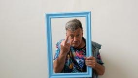 滑稽的资深人畸形人从画象框架和展示舌头和中指看 影视素材