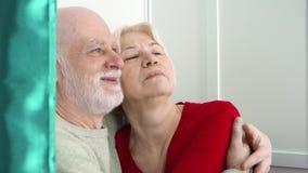滑稽的资深夫妇在摆在为照相机的照片摊,亲吻,做获得傻的面孔乐趣 影视素材
