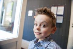 滑稽的逗人喜爱的小孩画象有被弄乱的头发的户内 图库摄影