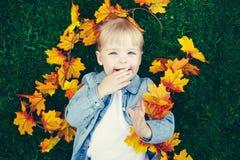 滑稽的逗人喜爱的微笑的白白种人小孩儿童女孩画象有说谎在与黄色秋叶的绿草的金发的 免版税图库摄影