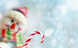 滑稽的雪人用在雪背景的糖果 新年好 免版税库存图片