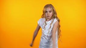 滑稽的青春期前的女孩跳舞,移动向在橙色背景隔绝的音乐 影视素材