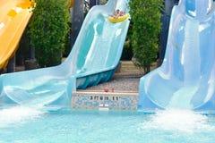 滑稽的childs有乐趣五颜六色的水滑道乘驾在水公园在国际推进地区 库存照片