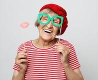 滑稽祖母穿红色衣裳的拿着falce玻璃和准备好党 免版税库存图片