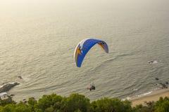 滑翔伞一前一后在一个蓝色降伞的飞行在鲜绿色的树衬托 库存照片