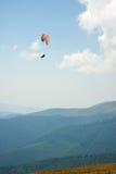 滑翔伞一前一后飞行在一个晴朗的总和的一个山谷 免版税库存照片