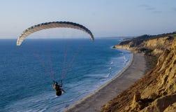 滑翔伞在浩大的海景采取,当滑动沿海滩和峭壁时 库存照片