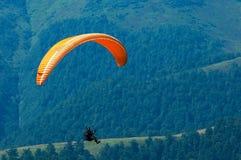 滑翔伞飞行在一个山谷在一个晴朗的夏日 免版税库存照片