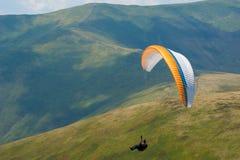 滑翔伞飞行在一个山谷在一个晴朗的夏日 库存图片
