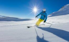 滑雪下坡在阿尔卑斯的年轻人 库存照片