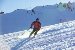滑雪下坡在高山的滑雪者反对日落 免版税库存照片