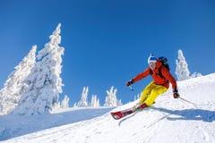 滑雪下坡在高山的滑雪者反对蓝天 免版税库存图片