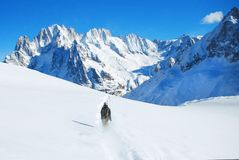 滑雪下坡在高山的滑雪者反对阳光 免版税图库摄影
