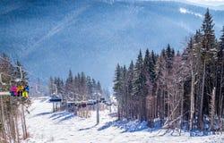 滑雪倾斜和现代升降椅的游人 在滑雪胜地Bukovel的假日 免版税库存照片