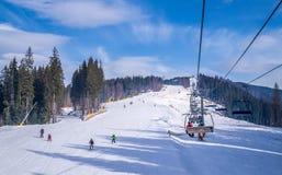 滑雪倾斜和现代升降椅的游人 在滑雪胜地Bukovel的Otdih 库存图片