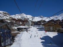 滑雪倾斜和驾空滑车在Val Thorens,滑雪在村庄中间的人们 图库摄影