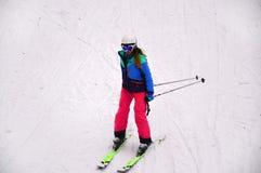 滑雪在小山下的女性滑雪者在Bukovel,乌克兰 库存照片