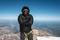 滑雪帽的一名登山家和有是冷的在山顶部的敞篷的下来夹克 免版税库存照片
