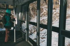 滑雪电缆车客舱的人,保持金属棒,看窗口 免版税库存图片