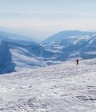 滑雪者下坡多雪的倾斜和山的在阴霾在冷的wint 库存图片