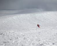 滑雪者下坡多雪的freeride倾斜和阴暗有薄雾的天空的是 免版税库存图片