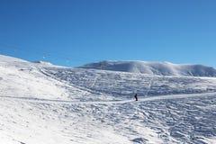 滑雪者下坡滑雪倾斜的在好太阳早晨 免版税库存照片