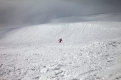 滑雪者下坡freeride倾斜和阴暗有薄雾的天空的在b前 库存照片