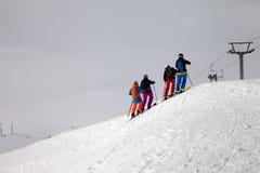滑雪者前面下坡滑雪场地外的倾斜和阴暗有薄雾的天空的 免版税库存照片