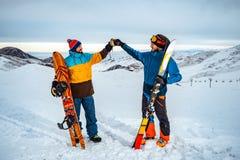 滑雪者和挡雪板互相招呼 他们做连接他们的拳头的一个友好的姿态 免版税库存照片