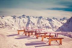 滑雪者和挡雪板的小咖啡馆在高加索, Dombai的山的上面在一个冬天晴天 被定调子的图象 免版税图库摄影