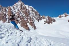 滑雪者在冰川的人滑雪或与新鲜的粉末的多雪的倾斜 欧洲阿尔卑斯勃朗峰断层块登上 冬天晴天 免版税库存照片