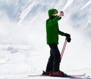 滑雪者在照相机做selfie打电话和在雾的多雪的山 免版税库存图片