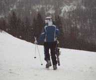 滑雪者步行沿着向下与滑雪的倾斜在他的在雪的手上 免版税库存照片
