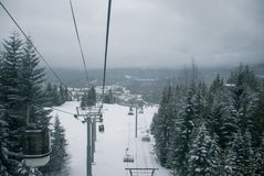 滑雪驾空滑车和长平底船上升积雪的山之间 库存图片
