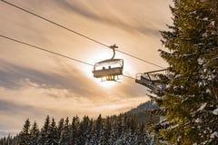 滑雪驾空滑车的滑雪者在太阳和天空蔚蓝的背景 免版税库存照片