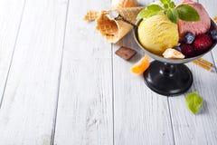 滚保龄球与与白色,黄色,红颜色和奶蛋烘饼锥体,巧克力三个不同瓢的冰淇凌, 免版税库存照片