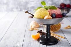 滚保龄球与与黄色,红颜色和奶蛋烘饼锥体,巧克力三个不同瓢的冰淇凌, 库存照片