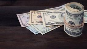 滚动一百美元在背景系列美国金钱5,10, 20, 50,在棕色木背景的新的100美金 免版税库存照片
