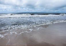 滚动在与山的海滩上的波浪在横跨水和风雨如磐的天空的天际 免版税库存图片
