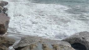 滚动在与岩石的含沙海岸,自然,慢mo的力量的泡沫似的海浪 股票视频