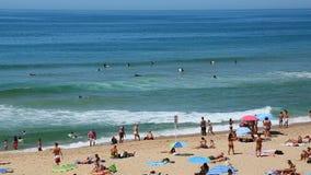 滚动在与晒日光浴的人,游泳在海洋,休息的冲浪者的海滩上的波浪 影视素材